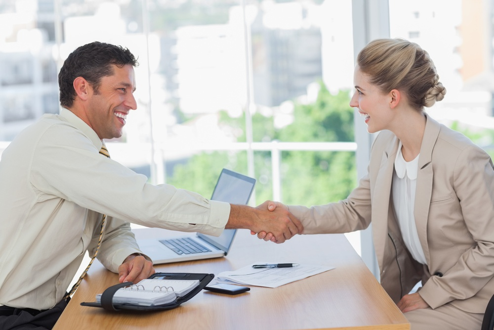 Blonde woman shaking hands while having an interview in office.jpeg